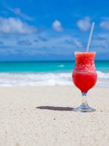 Red cocktail on a yellow sandy beach